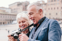 Tourist couple reviewing digital camera in town square, Siena, Tuscany, Italy 11015327907| 写真素材・ストックフォト・画像・イラスト素材|アマナイメージズ