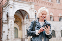 Mature woman looking at smartphone in city, Siena, Tuscany, Italy 11015327909| 写真素材・ストックフォト・画像・イラスト素材|アマナイメージズ
