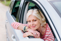 Portrait of mature woman looking out of car window on roadside 11015327946| 写真素材・ストックフォト・画像・イラスト素材|アマナイメージズ