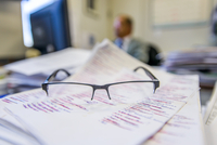 Pair of glasses on paperwork in office, close up 11015329259| 写真素材・ストックフォト・画像・イラスト素材|アマナイメージズ