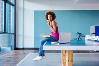 Young woman sitting on table tennis table looking at laptop and eating pizza 11015330670| 写真素材・ストックフォト・画像・イラスト素材|アマナイメージズ