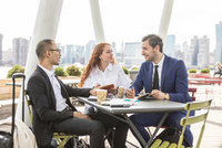 Businessmen and woman meeting at waterfront cafe with New York skyline, USA 11015331122| 写真素材・ストックフォト・画像・イラスト素材|アマナイメージズ