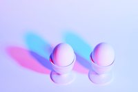 Two eggs in eggcups on purple background