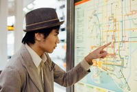 Young man looking at train map at train station 11015331617| 写真素材・ストックフォト・画像・イラスト素材|アマナイメージズ
