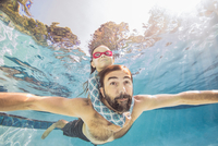 Underwater view of mature man swimming with daughter on piggy back 11015331714| 写真素材・ストックフォト・画像・イラスト素材|アマナイメージズ