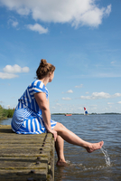 Woman sitting on jetty in the Frisian lake district in vintage dress, Sneek, Friesland, Netherlands 11015332105| 写真素材・ストックフォト・画像・イラスト素材|アマナイメージズ