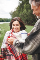 Mature couple standing in rural setting, holding hot drink, woman wrapped in blanket 11015332998| 写真素材・ストックフォト・画像・イラスト素材|アマナイメージズ