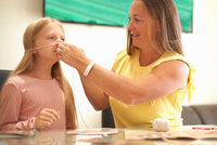 Mother and daughter sitting at table, mother measuring daughter's face with string 11015334595| 写真素材・ストックフォト・画像・イラスト素材|アマナイメージズ