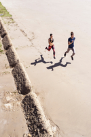 Young man and woman running along beach, elevated view 11015334704| 写真素材・ストックフォト・画像・イラスト素材|アマナイメージズ