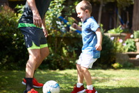 Father and son playing football in garden 11015334832| 写真素材・ストックフォト・画像・イラスト素材|アマナイメージズ