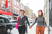 Two retro styled young women strolling on city street holding hands 11015335521| 写真素材・ストックフォト・画像・イラスト素材|アマナイメージズ