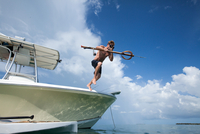Man jumping into water from boat, carrying fishing spear 11015335604| 写真素材・ストックフォト・画像・イラスト素材|アマナイメージズ
