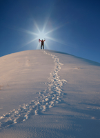 Mountain climber at top of snow capped mountain, arms raised, celebrating, Zermatt, Valais, Switzerland, Europe