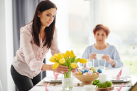Mid adult woman arranging yellow tulips at easter dining table 11015337403| 写真素材・ストックフォト・画像・イラスト素材|アマナイメージズ