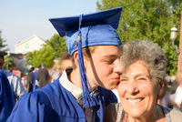 Teenage boy kissing grandmother at graduation ceremony