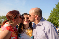 Parents kissing daughter at graduation ceremony