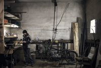 Mechanic looking at workbench in workshop with dismantled vintage motorcycle 11015339204| 写真素材・ストックフォト・画像・イラスト素材|アマナイメージズ