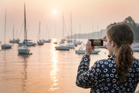 Rear view of woman photographing boats at sunset, Lazise, Veneto, Italy, Europe 11015340989| 写真素材・ストックフォト・画像・イラスト素材|アマナイメージズ
