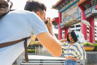 Young male tourist photographing girlfriend by temple, Bangkok, Thailand 11015342543| 写真素材・ストックフォト・画像・イラスト素材|アマナイメージズ