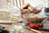 Table with fresh bread, cheeses and vine tomatoes 11015343377| 写真素材・ストックフォト・画像・イラスト素材|アマナイメージズ
