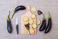 Slices of aubergine on chopping board, with knife and whole aubergines, overhead view 11015343700| 写真素材・ストックフォト・画像・イラスト素材|アマナイメージズ