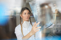 Young female doctor looking at hospital xray 11015344647| 写真素材・ストックフォト・画像・イラスト素材|アマナイメージズ