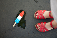 Girl wearing red sandals with ice lolly on floor