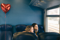 Couple with heart shaped balloon looking out window of train
