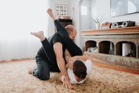 Couple wrestling on carpet at home