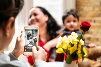 Boy taking smartphone photo mother and toddler brother celebrating mothers day, over shoulder view 11015363098| 写真素材・ストックフォト・画像・イラスト素材|アマナイメージズ