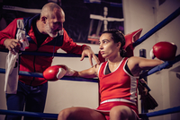 Boxing coach talking to female boxer sitting in boxing ring.