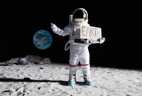 An astronaut on the moon with his thumb out, holding 'EART 11016020221| 写真素材・ストックフォト・画像・イラスト素材|アマナイメージズ
