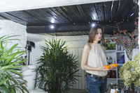 Female owner holding artificial pumpkins at decor shop 11016031612| 写真素材・ストックフォト・画像・イラスト素材|アマナイメージズ