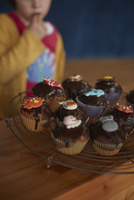 Cupcakes on cooling rack at table with girl standing in background 11016036952| 写真素材・ストックフォト・画像・イラスト素材|アマナイメージズ