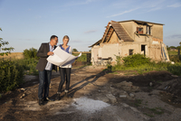 Woman standing with estate agent while reading documents against house on sunny day 11016037294| 写真素材・ストックフォト・画像・イラスト素材|アマナイメージズ