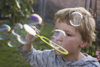 Close-up of boy blowing bubbles with wand in backyard 11016038649| 写真素材・ストックフォト・画像・イラスト素材|アマナイメージズ