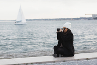 Full length of woman sitting on promenade photographing by water, Lisbon, Portugal 11016039303| 写真素材・ストックフォト・画像・イラスト素材|アマナイメージズ