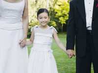 newlyweds holding flower girl's hands
