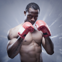 Back lit African boxer with arms raised 11018078603| 写真素材・ストックフォト・画像・イラスト素材|アマナイメージズ