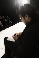 Caucasian man text messaging on cell phone during fashion show 11018078739| 写真素材・ストックフォト・画像・イラスト素材|アマナイメージズ