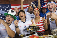 Sports fans drinking and eating in sports bar 11018078962| 写真素材・ストックフォト・画像・イラスト素材|アマナイメージズ
