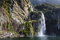 Waterfall over sheer cliffs to remote river, Te Anau, Southland, New Zealand 11018088109| 写真素材・ストックフォト・画像・イラスト素材|アマナイメージズ