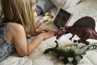 Caucasian girl laying on bed with toy dinosaurs using digital tablet 11018094937| 写真素材・ストックフォト・画像・イラスト素材|アマナイメージズ