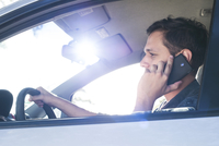 Driver using cell phone without hands-free device while driving 11025008733| 写真素材・ストックフォト・画像・イラスト素材|アマナイメージズ