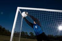 Young female soccer goalie catching ball