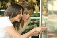 Hispanic woman and daughter window shopping