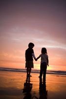 Brother and sister holding hands on beach at sunset