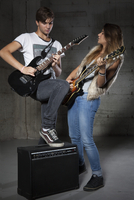 Young Man and Teenage Girl Playing Electric Guitars