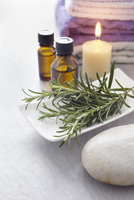 Sprig of rosemary, fresh herbs, candle, towel and bottles of