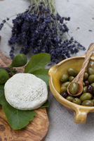 Cheese round of Tome de Provence, goat cheese on cutting board with bowl of olives and bundle of lavender, Provence, France 11030040698| 写真素材・ストックフォト・画像・イラスト素材|アマナイメージズ